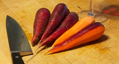 Red carrots and knife on the cutting board.